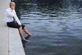 Businessman sitting on wall by lake, using mobile phone — Stock Photo