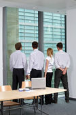 Verksamhet team tittar genom fönstret på kontoret — Stockfoto