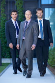 Portrait of businessmen walking in suit — Stock Photo