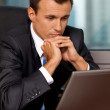 Businessman using laptop with hand on chin in office — Stock Photo