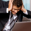 Businessman using laptop with head in hands — Stock Photo