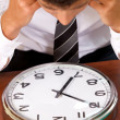 Businessman looking at clock in office with head in hands — Stock Photo #3820145
