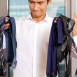 Businessman choosing tie at office — Stock Photo