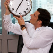 Businessman looking at clock in office — Stock Photo #3820523