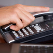 Close-up of hand holding landline phone in office - Stock Photo