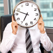 Businessman holding clock over face — Stock Photo #3820699