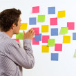 Businessman sticking sticky notes on wall — Stock Photo