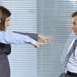 Businesswoman shouting at businessman in office - Stock Photo