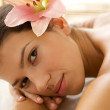 Portrait of young woman relaxing on massage table - Stok fotoğraf