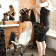 Female hairdresser adjusting curlers in young woman's hair — Stock Photo