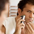 Reflection of young man in mirror shaving with electric shaver — Stock Photo #3821101