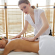 Portrait of young woman receiving massage from masseuse - Stock Photo