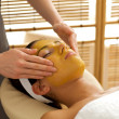 Young woman receiving facial treatment in spa - Stock Photo