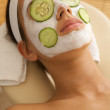 Young woman lying down on massage table with cucumbers on eyes and face - Stock Photo