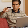 Young man holding credit card and using laptop — Stock Photo