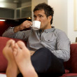 Young man drinking tea, sitting in sofa — Stock Photo