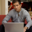 Portrait of young man with laptop — Stock Photo