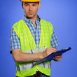Architect in coveralls and hardhat using clipboard — Stock Photo