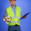 Architect in coveralls holding blueprint and clipboard — Stock Photo