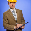 Portrait of businessman in yellow hardhat writing on clipboard — Stock Photo