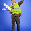 Businessman in coveralls holding blueprint and pointing — Stock Photo