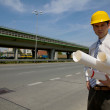 Portrait of architect in hardhat holding blueprint at construction site — Stock Photo #3822129