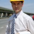 Portrait of architect in hardhat holding blueprint at construction site — Stock Photo #3822130