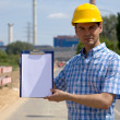 Portrait of architect holding clipboard at construction site — Stock Photo