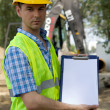 Stock Photo: Portrait of architect holding clipboard at construction site