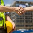 Architects shaking hand at construction site - Stock Photo