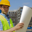 Portrait of engineer holding blueprint at construction site — Stock Photo