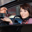 Portrait of young woman receiving the car keys from car salesman — Stock Photo