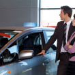 Car salesman and female customer looking at new car — Stock Photo