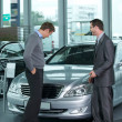 Car salesperson explaining car features to customer — Stockfoto