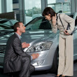Car salesperson showing car features to customer - Stock Photo