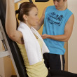 Stock Photo: Young womexercising with personal trainer