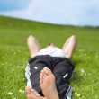 Young man lying on grass in park — Stock Photo