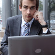 Young caucasian businessman using his laptop in cafe — Stock Photo