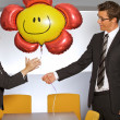 Stock Photo: Businessmgiving balloon to businesswomin office