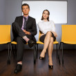 Portrait of businessman and businesswoman sitting in waiting room — Stock Photo