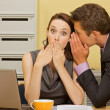 Businessman whispering in businesswoman's ear at office — Stock Photo