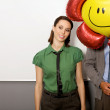 Businesswoman and businessman at office, man's face obscured with balloon - Stock Photo