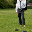 Businessman standing in park, eyes closed -  