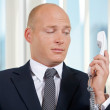 Businessman holding telephone receiver at office - Stock Photo