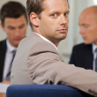 Portrait of businessman while other business in background - Stock Photo
