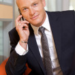 Businessman conversing on mobile phone, portrait - Stock Photo