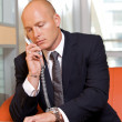 Businessman conversing on landline phone -  