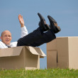 Portrait of cheerful young man sitting in cardboard box at park - Stock fotografie