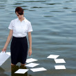 Businesswoman standing in lake with papers floating on water - Stock Photo