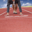 Businesswoman on start line of a running track — Stock Photo